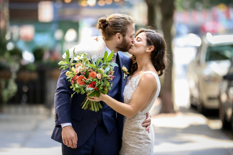 Couple kiss with bouquet